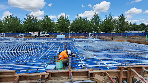 Man working on radiant heating floor installation to new building