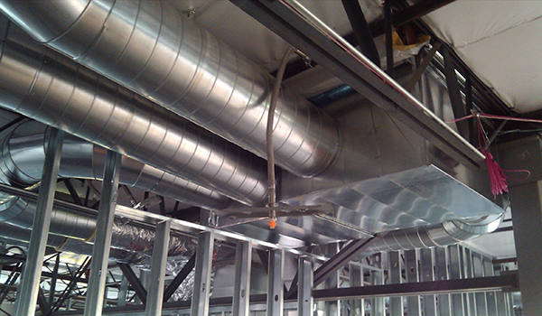 Close up of exposed HVAC system along ceiling.