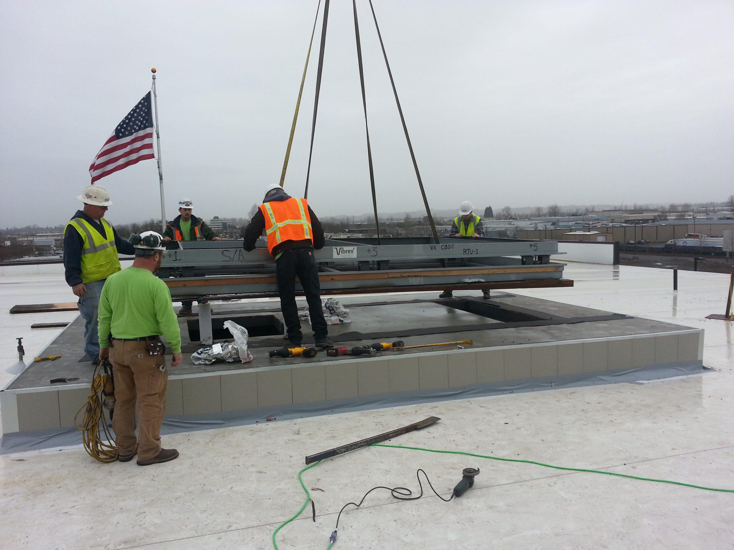 Men on roof wearing reflective vest installing large beams.